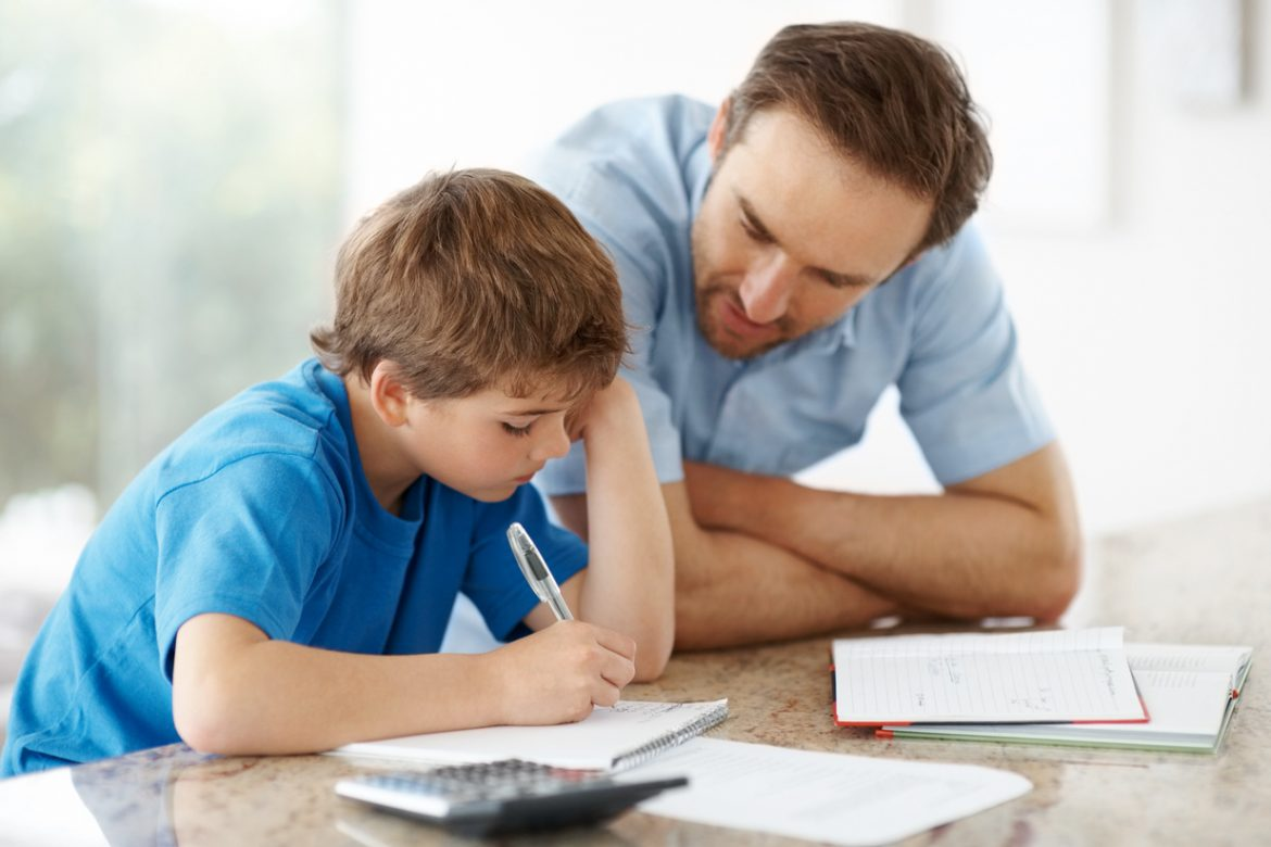 Young man assisting his little son with some home work